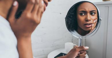 pretty african american woman looking at mirror while suffering from tooth pain
