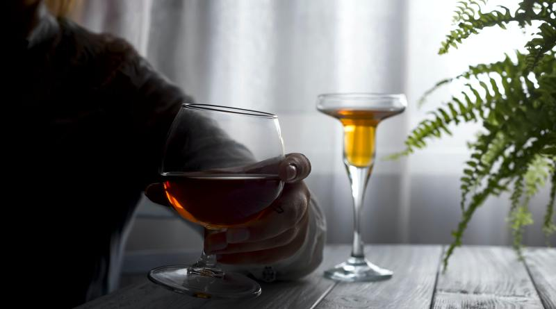silhouette of anonymous alcoholic woman person drinking behind glass of alcohol.