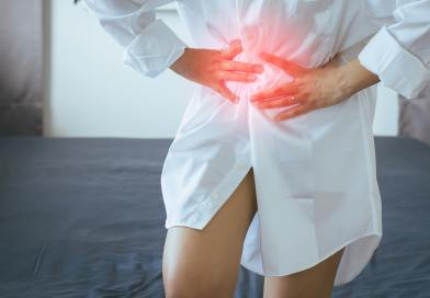 Woman having painful stomachache at home