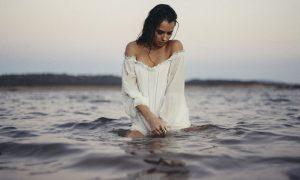 Una mujer vestida de blanco se baña en el mar. Transcender el conflicto y la culpa