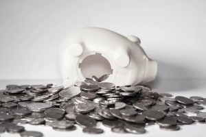A piggy bank with coins spilling out of it.