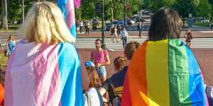 back of 2 adults wearing trans flag and rainbow flag and children
