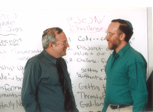 Rabbis Jeffrey Schein and Brian Nevins-Goldman in front of a white board covered with writing