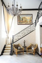 """Custom wrought iron stairs, reupholstered antique chairs, leopard print, pugs, 24"""" x 24"""" floor tile, Italian plaster walls"""