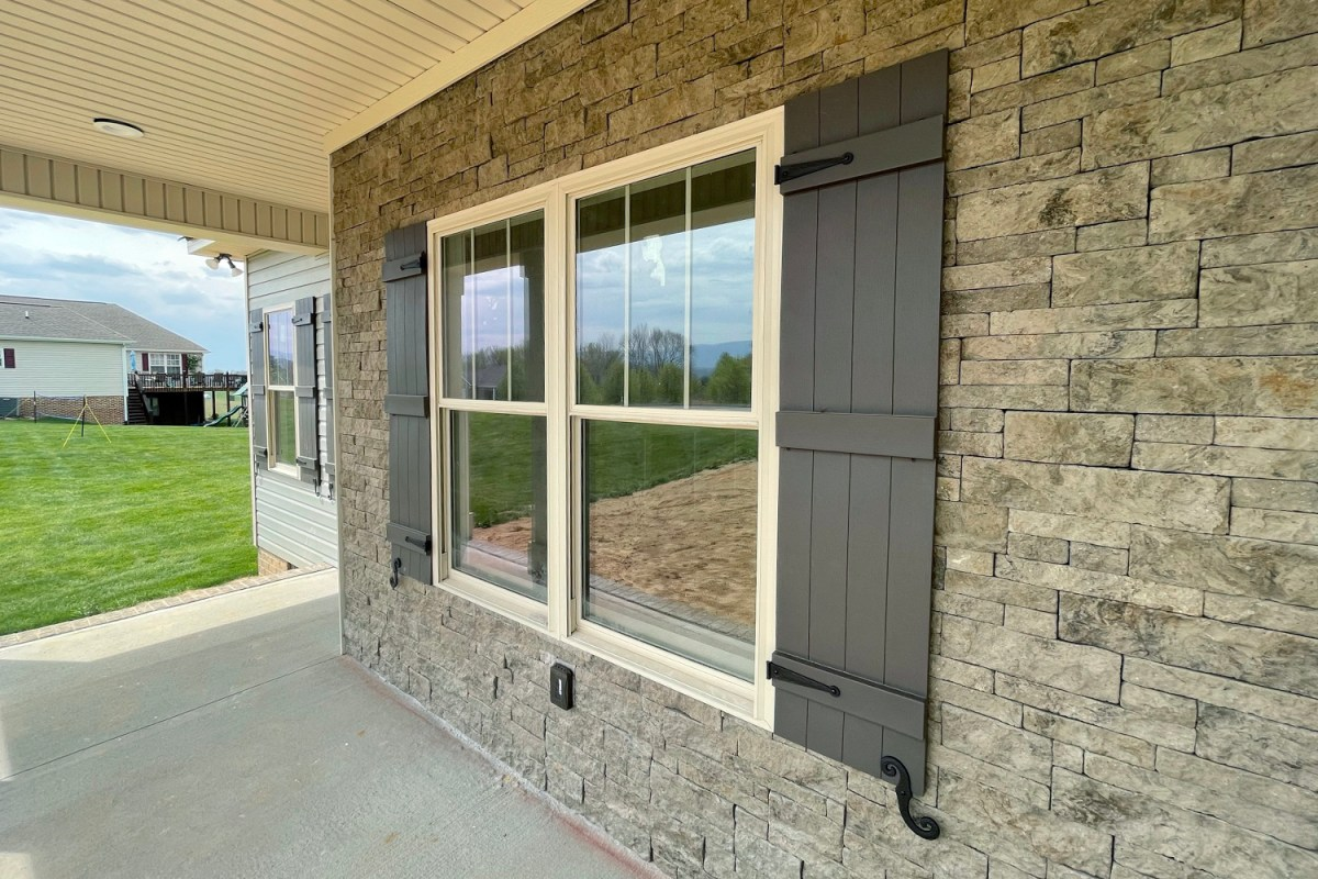 Mortarless Stone Veneer installed on exterior of home around window with white trim and dark shingles