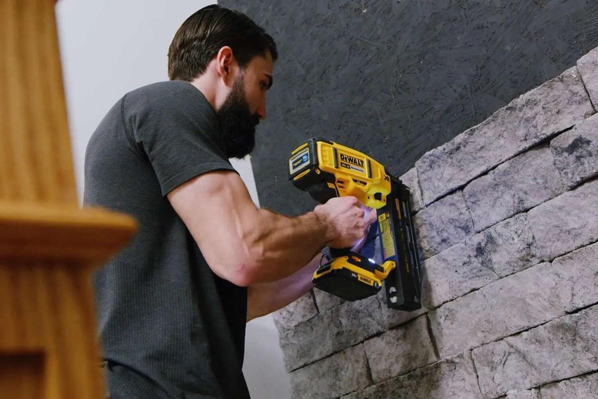 main with yellow nailing gun installing stone veneer to wall