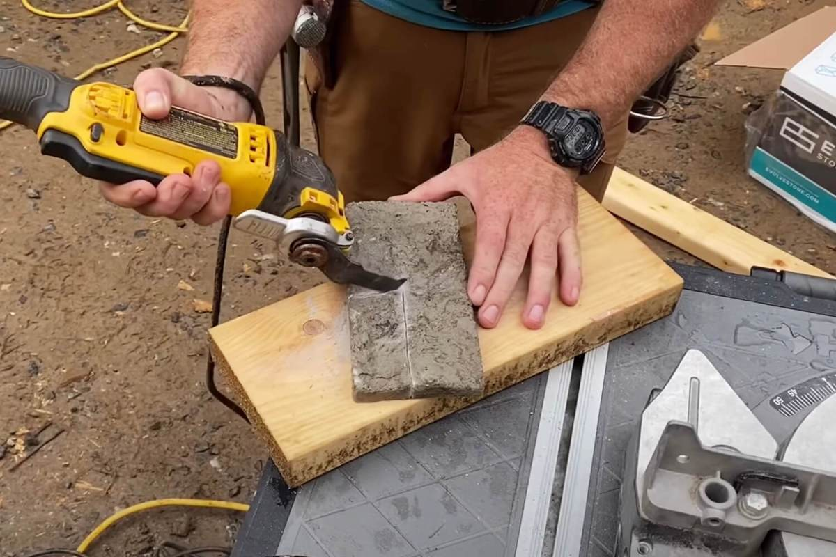 Close up of man using a power tool to cut stone veneer