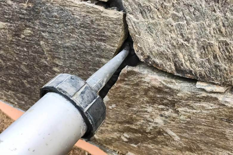 tube with grout being applied in between the space of stones