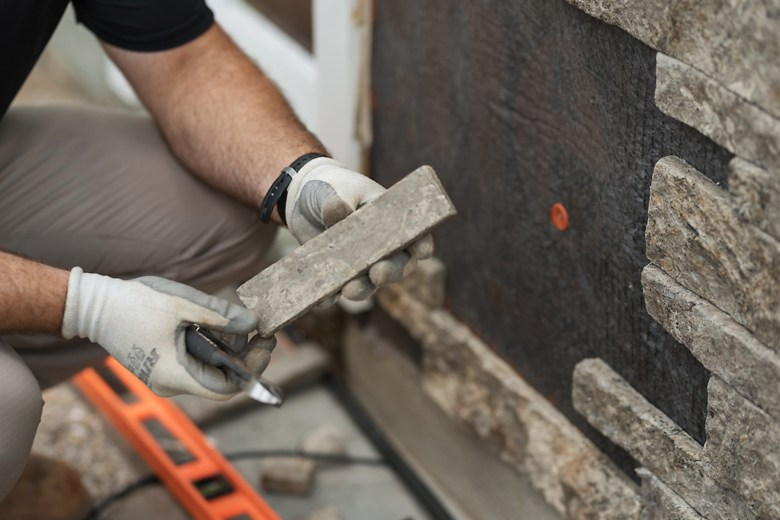 close up of man holding single stone veneer to install on wall