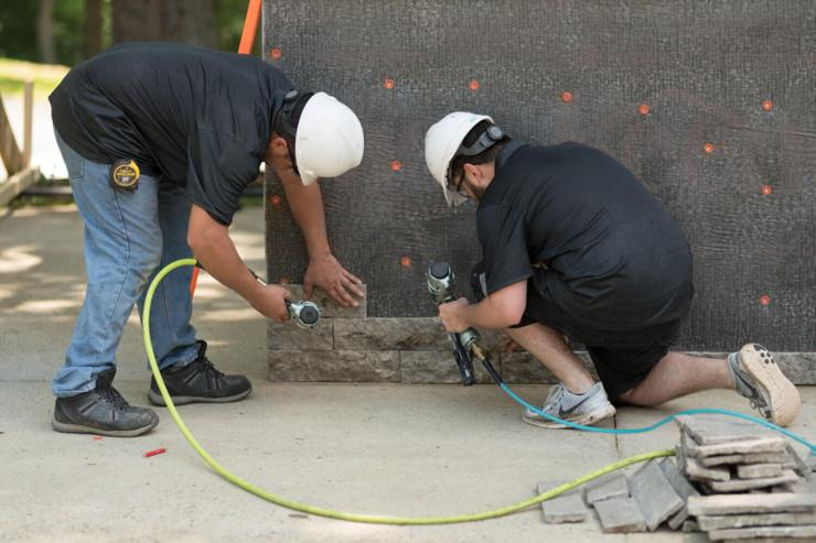 two men in back shirts installing stone veneer to wall