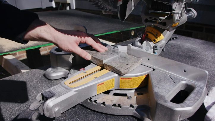 close up of person cutting evolve stone piece to size with saw