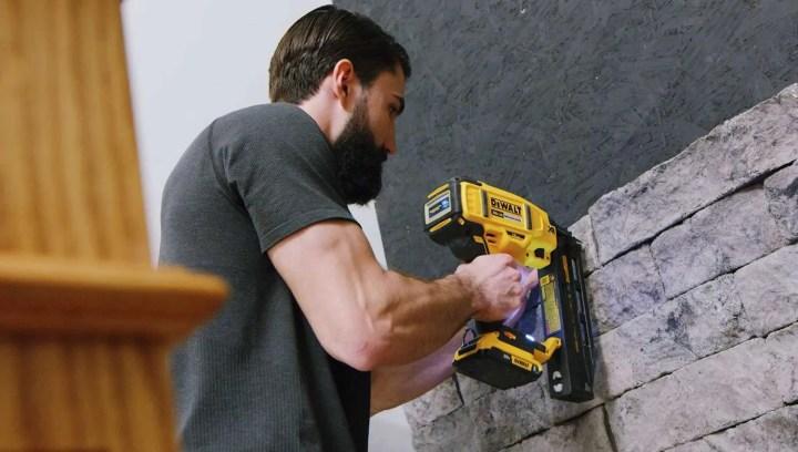 man with yellow nailgun begins to install faux stone veneer onto wall