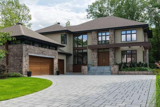 brown house with exterior stone veneer on garage and pillars of doorway