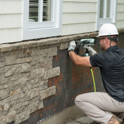 Man with hard hat installing Evolve Stone with a nail gun