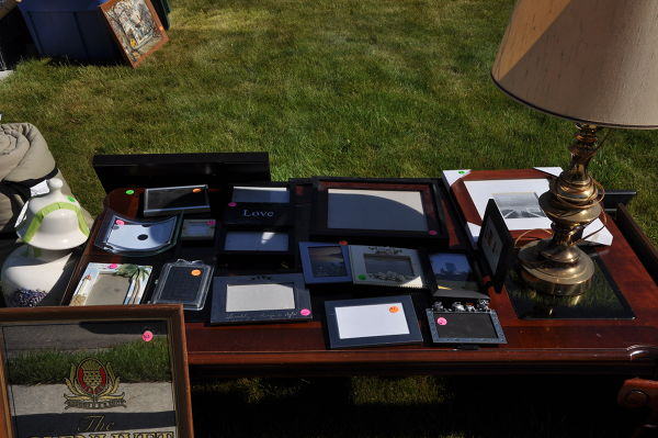 Lots of picture frames on table being sold in yard sale before moving into an RV to travel the country.