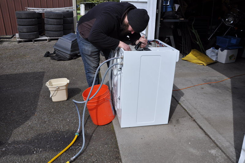 Running a test on our Splendide 6000 washer outside the garage before replacing water inlet valves.
