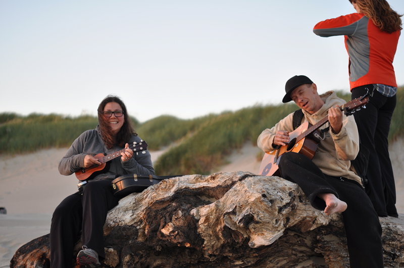 Adrianne and Dave playing guitar and ukelele on the beach at sunset on our full time RV adventure.