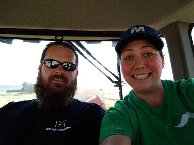 A selfie of Adrianne and Adam sitting in the bank out wagon during Adams seasonal job working the wheat harvest as we travel the country living full time in our RV.