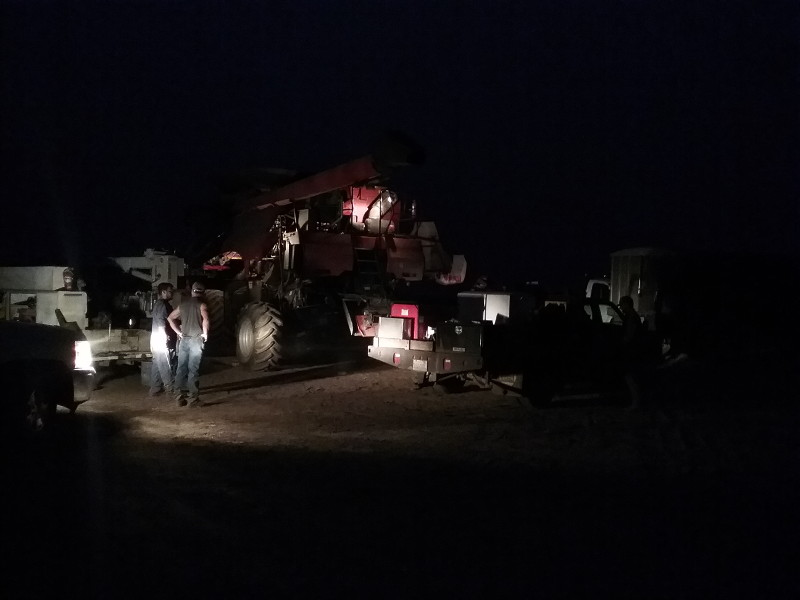 The combine is broke down with a pickup shining the headlights on it to be able to see in the dark, it's around 10 pm.