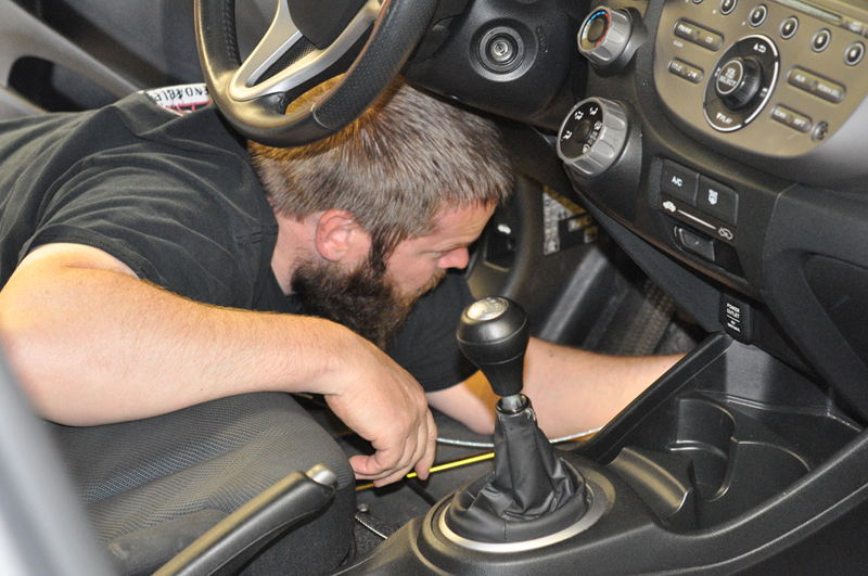 Adam squeezing under the dash to install the Ready Brake cables while setting up the RV tow car to travel the country.
