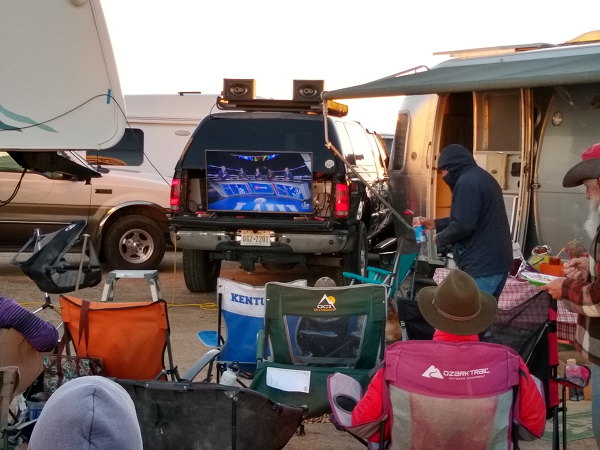 Big screen tv and speakers on the tailgate of a pickup for watching the superbowl with a crowd of 20 people.