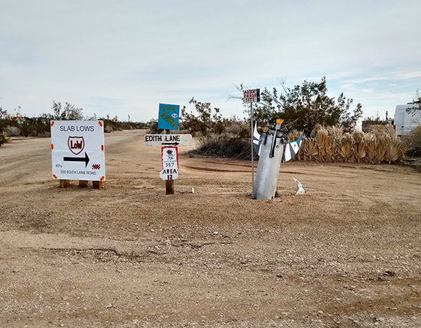 Street signs within Slab City, one looks like an old missle sticking partially out of the ground.