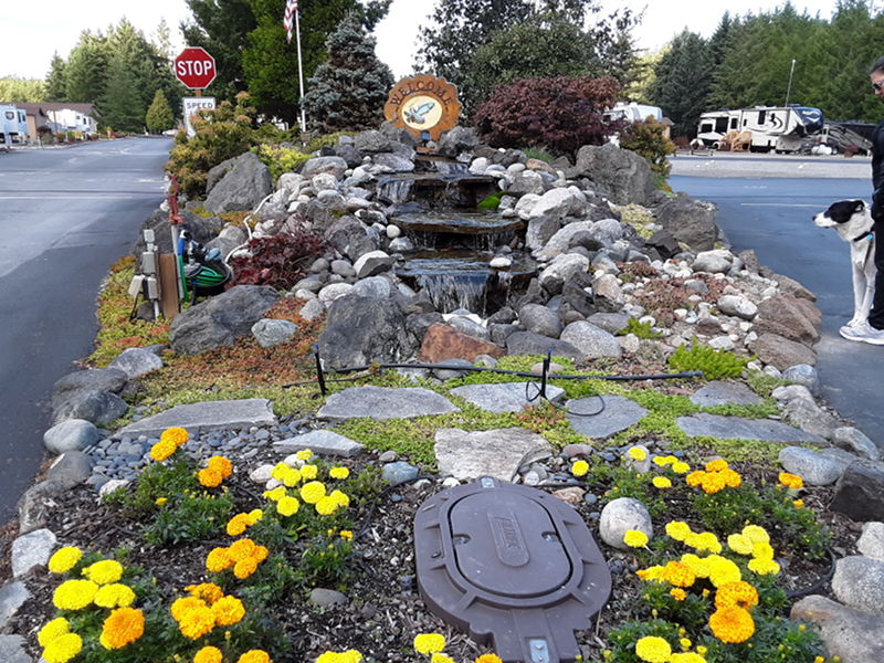 Evergreen Coho SKP Co-ops beautiful entrance with flowers and water feature.