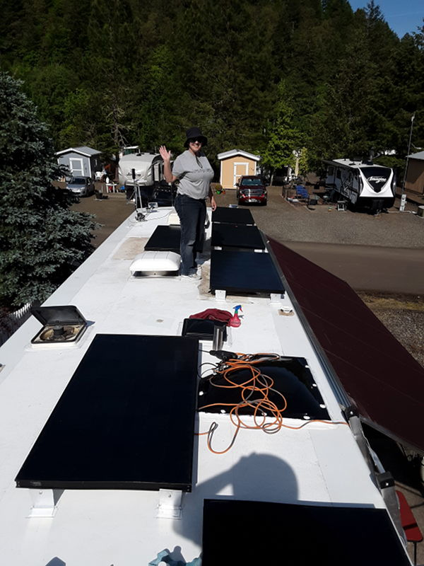 Our new solar panels being installed on the roof with Adrianne waving.