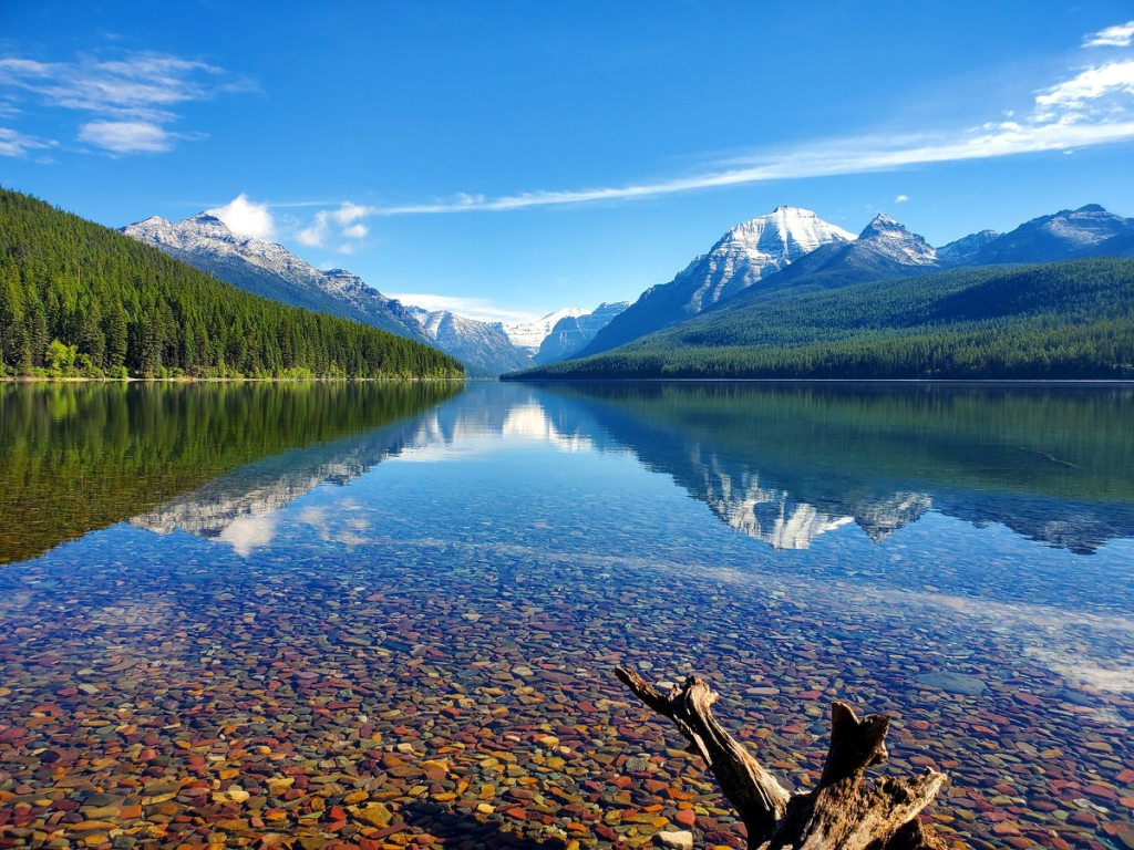 Bowman Lake in Glacier National Park in the early morning hours with reflection of mountains in the lake.