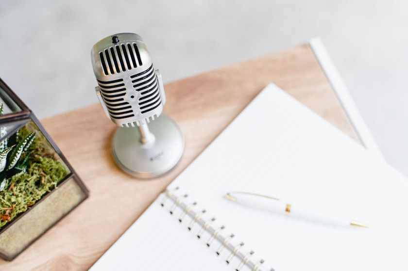 Open notebook with a white and gold pen on a wooden desk - above the notebook are a silver microphone and a potted plant.