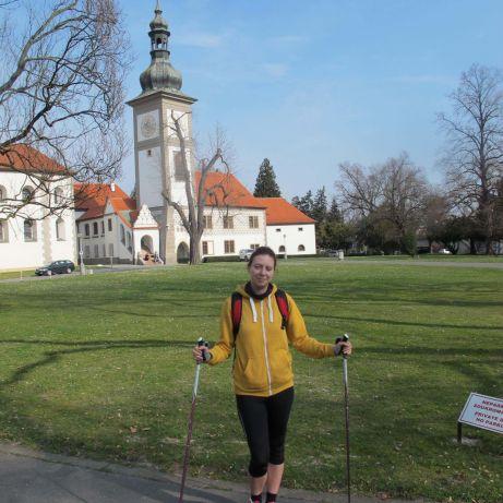 Autorka bloga stoi zkijkami donordic walking natle żółto-białego zamku w Zbraslawiu.