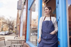 Smiling Female Small Business Owner Standing In Shop Doorway On Local High Street