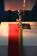 Sewing the gold braid to the edges of the red trim