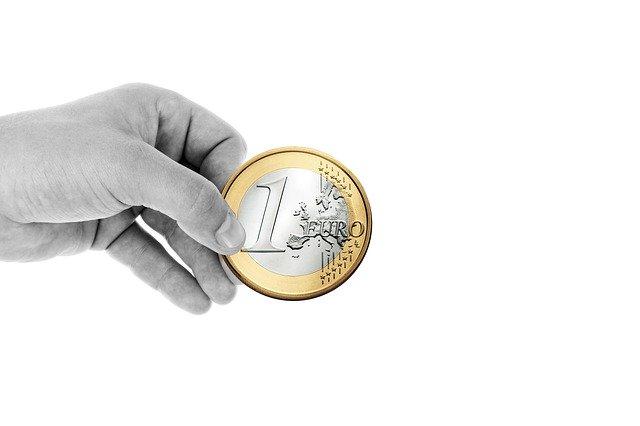 Main qui tient une pièce de 1 euro. Une pièce pour trouver la Probabilité du Lancer de Pièce de monnaie
