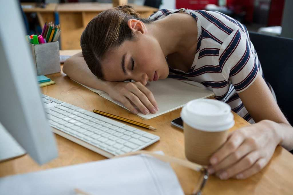 Student slumped over desk sleeping with coffee in hand