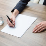 closeup-of-a-business-womans-hands-while-writing-down-some-essential-information-a-glass-of-water-paper-and-a-pen-a-concept-of-57698082