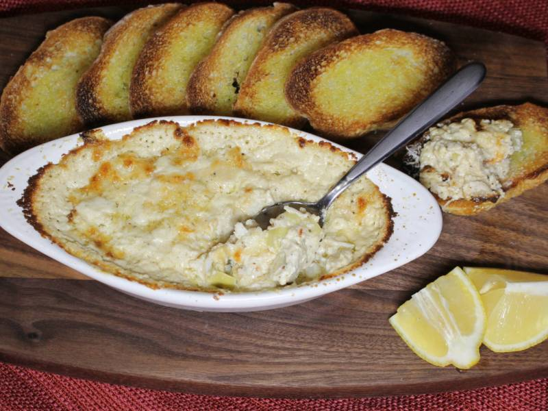 Spoon in a bowl of baked crab and artichoke dip with toasted baguette slices and lemon