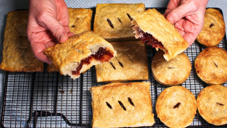 hands holding a torn in half hand pie showing cherry filling and flaky crust