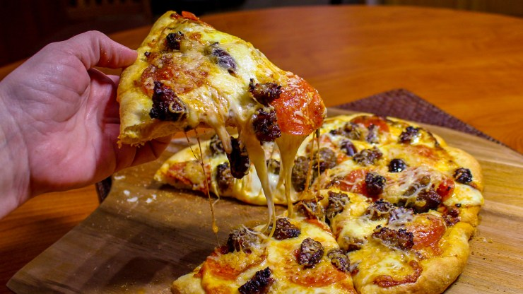 Hand lifting a slice of homemade pizza with pepperoni and sausage