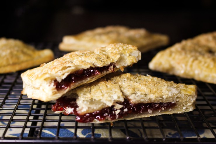 Cross section image of cherry hand pie with flaky crust and sugar crystals