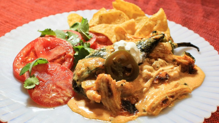 Plate with Chicken Enchilada Stuffed Poblano Pepper with sliced tomatoes and tortilla chips