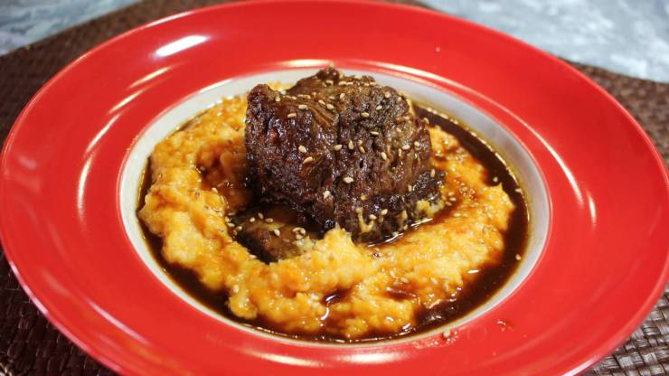 Beef short rib on a bed of butternut squash polenta covered in sauce