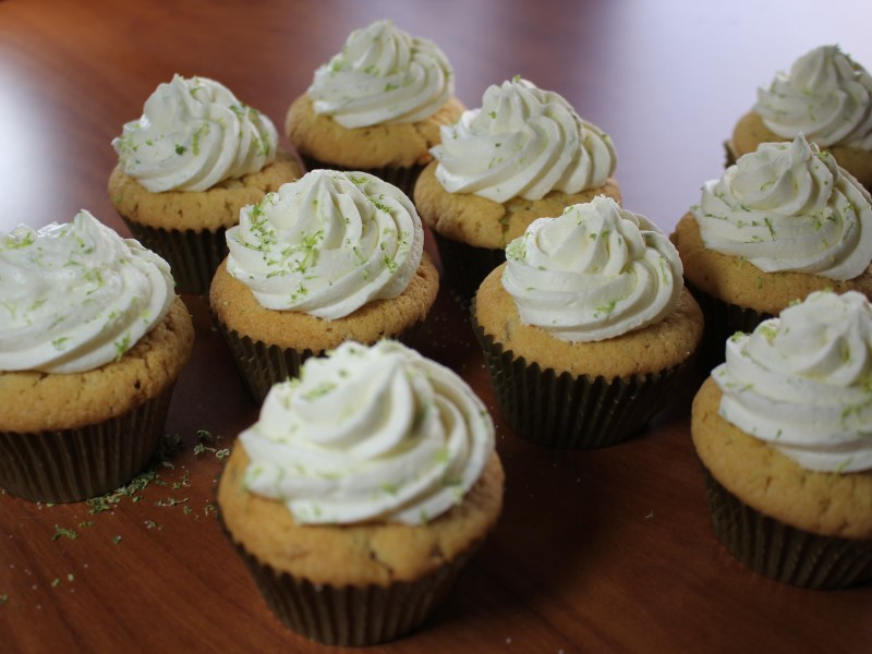 Ten cupcakes each topped with a swirl of icing and lime zest