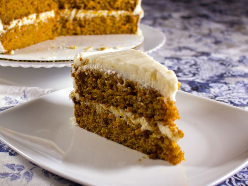 Slice of a two-layer carrot cake with cream cheese frosting on a plate, with the full cake in the background