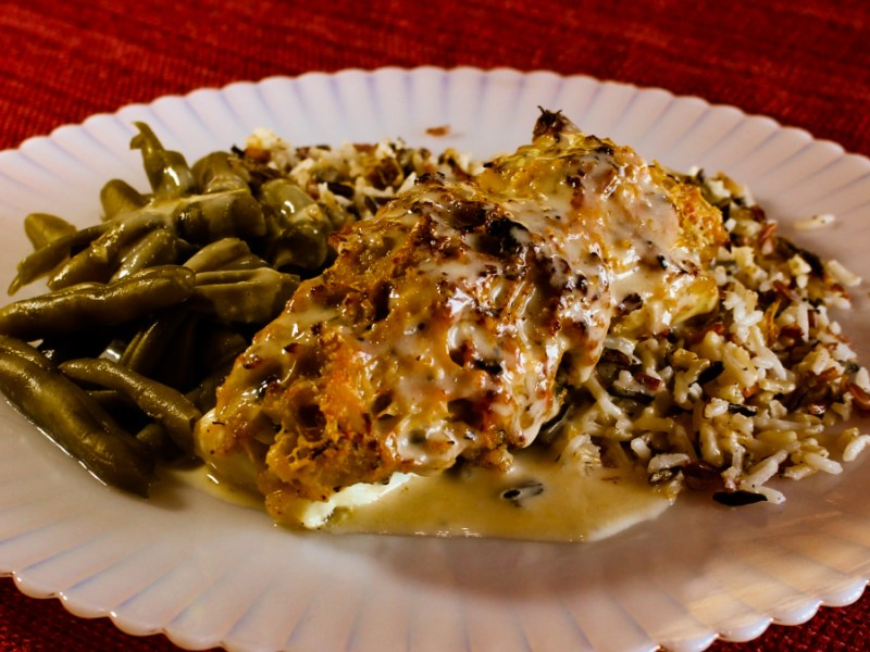 Baked halibut topped with deviled crab and a lemon butter sauce on a plate with rice and green beans