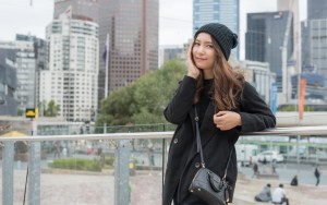 young Asian women standing with Melbourne skyline in the background