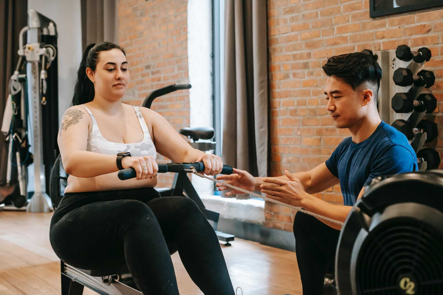 focused young asian male trainer helping overweight woman to do pulling exercise
