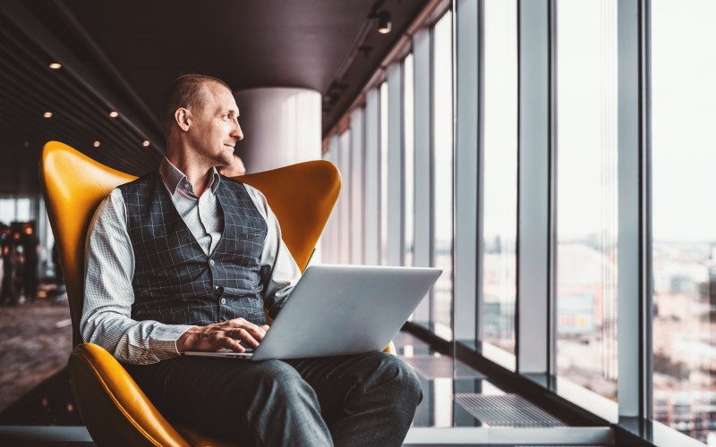 A handsome cheerful caucasian man entrepreneur is sitting with a laptop on his knees on an orange armchair next to the window indoors of a luxurious interior of a modern business office skyscraper