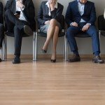 Businesspeople legs sitting in chair in queue wait job interview