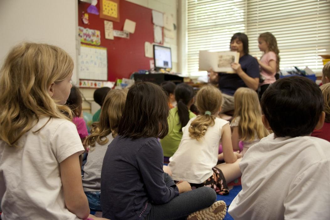Children in a classroom sat on the floor